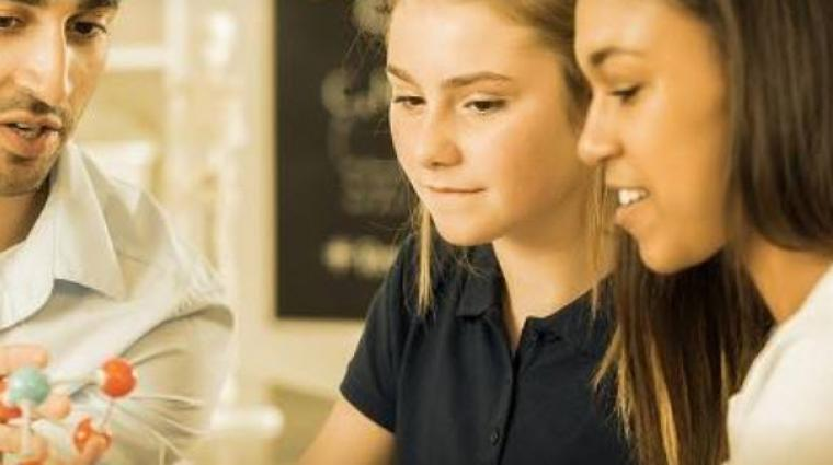 two girls looking at model of molecule